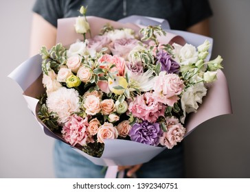 Very nice young woman holding huge beautiful blossoming bouquet of fresh carnations, eustoma, roses flowers in purple and pink colors on the grey background