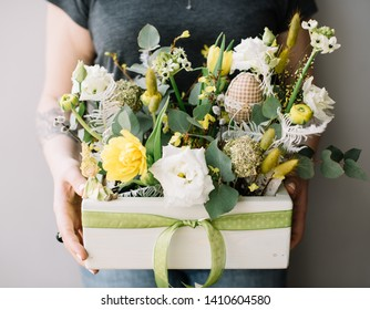 Very nice young woman holding big and beautiful easter box of fresh eustoma, tulips, ranunculus in white and yellow colors, decorated with eggs, cropped photo, bouquet close up