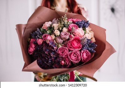 Very nice young woman holding big and beautiful bouquet of fresh hydrangea, roses, ranunculus, eucalyptus flowers in pink and purple colors, cropped photo, bouquet close up