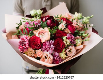 Very nice young woman holding big and beautiful bouquet of fresh eustoma, roses, ranunculus, carnations, peony in cream, pink and burgundy colors, cropped photo, bouquet close up