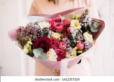 Very nice young woman holding big and beautiful bouquet of fresh roses, ranunculus, lilac peony, eustoma, eucauptus, statice, matthiola in pink and purple colors, cropped photo, bouquet close up
