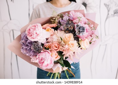 Very nice young woman holding big and beautiful bouquet of fresh roses, carnations, peony, matthiola in tender pink and purple colors, cropped photo, bouquet close up