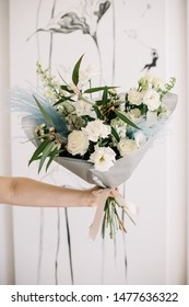 Very nice young woman holding big and beautiful bouquet of fresh iroses, eustoma, eucalyptus, delphinium in white color, cropped photo, bouquet close up
