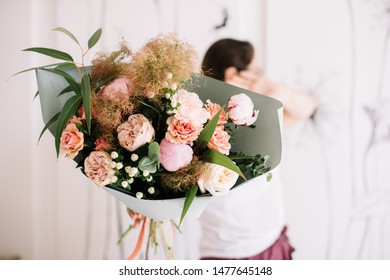 Very nice young woman holding big and beautiful bouquet of fresh brunia, roses, cotinus, peony, eucalyptus in white and pink colors, cropped photo, bouquet close up