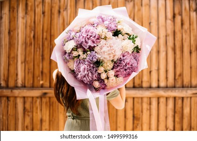 Very nice young woman holding big and beautiful bouquet of fresh hydrangea and roses in purple and cream colors, cropped photo, bouquet close up on the wooden background