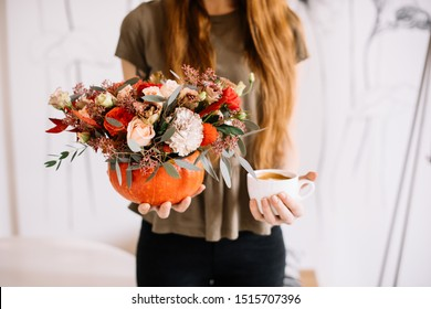 Very nice young woman holding in one hand big and beautiful pumpkin filled with pink and red roses, eustoma, carnations, eucalyptus flowers and in another hand a cup of hot cappuccino coffee