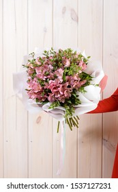 Very nice young woman holding big and beautiful fluffy bouquet, cropped photo, beautiful bouquet in woman's hand close-up on wooden background