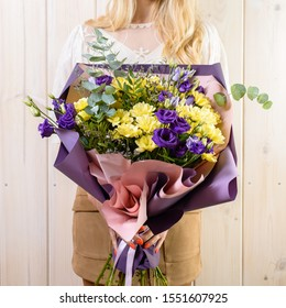 Very nice young woman holding big and beautiful fluffy bouquet, beautiful bouquet in woman's hand closeup on wooden background