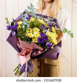 Very nice young woman holding big and beautiful fluffy bouquet, beautiful bouquet in woman's hand close-up on wooden background