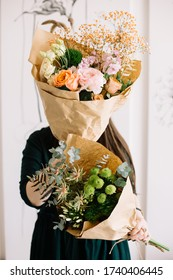 Very nice young woman holding two beautiful bunches of fresh roses, buttercups, eucalyptus, carnations, matthias, eustoma, fern, chrysanthemum flowers in pink, peach and green colors, bouquet close up