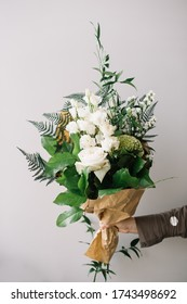 Very nice young woman holding big and beautiful bunch of fresh roses, fern, statice, greenery flowers in green and white colors, wrapped in craft paper, cropped photo, bouquet close up