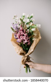 Very nice young woman holding big and beautiful bouquet of fresh campanula, delphinium and snapdragon flowers in white, pink and purple colors, cropped photo, bouquet close up