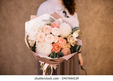 Very nice young woman holding big and beautiful bouquet of fresh peony, dahlia, chrysanthemum, carnations, eustoma, hydrangea flowers in white and peach colors, cropped photo, bouquet close up