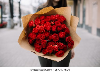 Very nice young woman standing outdoors, holding big and beautiful mono bouquet of fresh red roses, wrapped in craft paper, cropped photo, bouquet close up