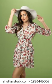 very nice young woman in summer floreal dress. with a white hat looking in camera . she posing on green background