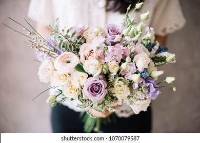 Very nice young woman in a white shirt holding blossoming flower bouquet of  fresh ranunculus, roses, carnations, eustoma in cream and purple colors on the grey wall background