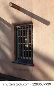 A very old adobe wall with exposed viga  and a window with wooden bars somewhere in Santa Fe, NM - vertical orientation
