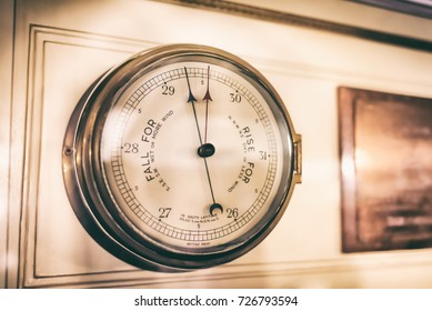 Very old aneroid barometer on the wall at the cabin of the sail ship; Vintage style effect