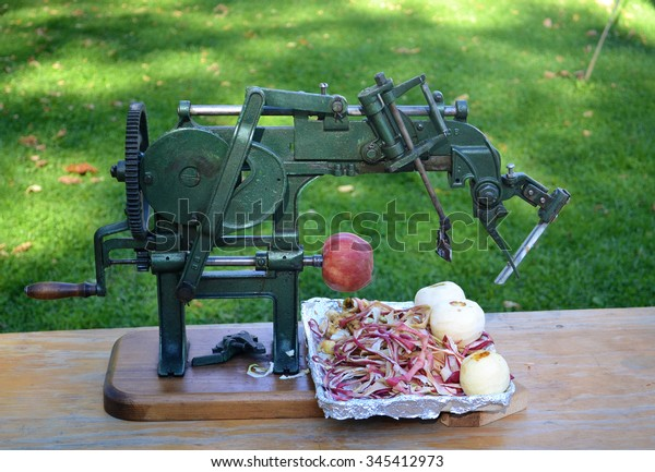 A very old and antique apple peeler sitting on a table with three peeledapples and one in works.
