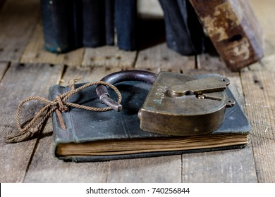 Very old book and key on an old wooden table. Old room, wooden table and book with key, black background