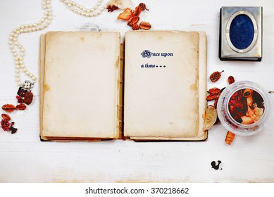 A very old book with stained pages is open, providing copy space, laying on a white washed, rustic wooden table. Flat lay perspective with horizontal composition. Feminine items surround the book