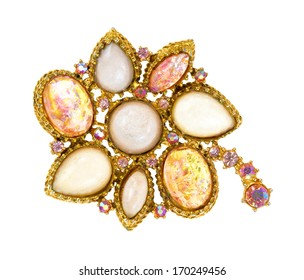 A very old brooch showing details on a white background.