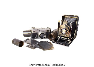 A very old camera (from the beginning of the XXth century) set with another old camera (from the fifties) and old film and negatives.