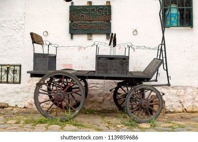 """A very old carriage parked at an old stone paved street of the colonial town of Villa de Leyva, in the Andean mountains of central Colombia. The singboard reads: """"Horses for rent"""", in spanish."""