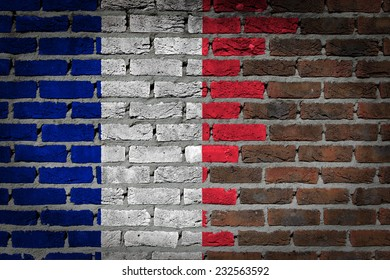 Very old dark red brick wall texture with flag - France