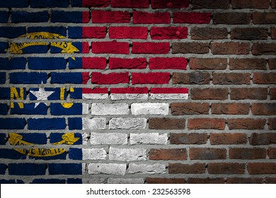 Very old dark red brick wall texture with flag - North Carolina