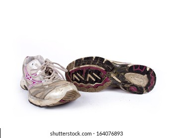 Very old dirty pair of running shoes over a white background
