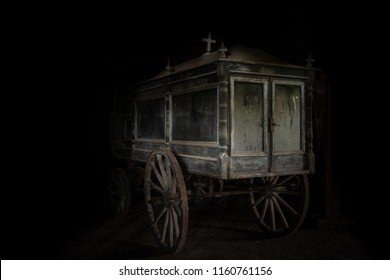 Very old and dusty hearse made of wood with large wooden wheels. Used to transport the coffin with the dead during the funeral in the late 18-th century.