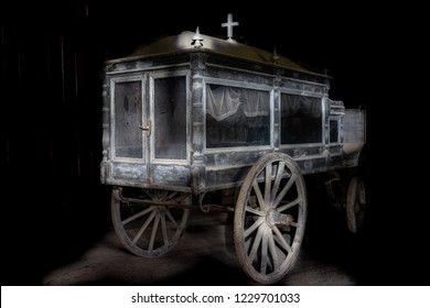 Very old and dusty hearse made of wood with large wooden wheels. Used to transport the coffin with the dead during the funeral a couple of hundred years ago