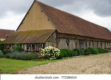 Very old fashion stone, bricks and wood barn in the countryside on a spring stormy day in France