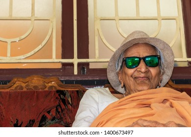 An very old Indian woman smiling happily, natural look with hat and coolers