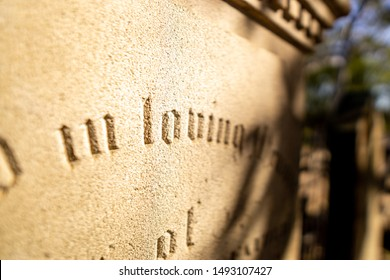 Very old Inscriptions etched into tomb stones in a cemetery. The text has been chiseled deep into the marble and stone of the gravestones in beautiful scripted font.