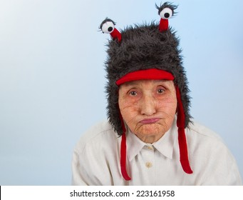 very old lady in funny fur hat with two tentacles with a bored, sulky expression