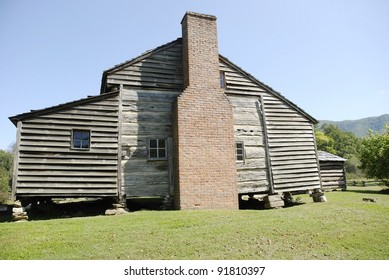 Very old log house has additions with rough plank siding.  Large brick chimney and natural (unpainted) finish.  Tourist attraction in Great Smoky Mountains National Park.