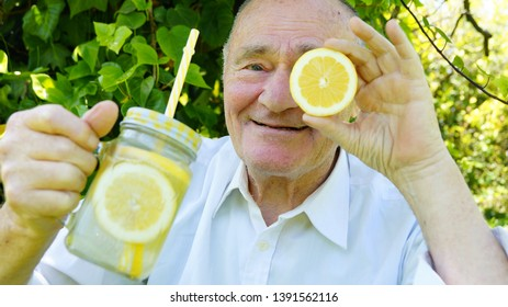 Very old man is drinking a homemade limonade with a yellow straw. Elderly gentleman drinks a lemon cocktail on green vegetation background.The concept of a healthy lifestyle and natural nutrition.