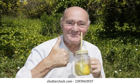 Very old man is drinking a homemade limonade with a yellow reusable boba straw. Elderly gentleman drinks a lemon cocktail on green vegetation background.The concept of a healthy lifestyle and natural