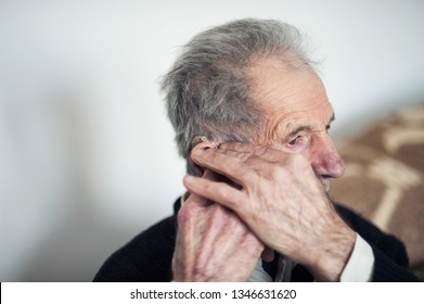 Very old man having a hearing problems and placing a hearing device into his ear