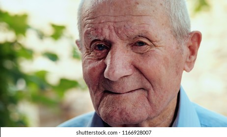Very old man portrait with emotions. Grandfather is smiling and looking to camera. Portrait: aged, elderly, senior. Close-up of old man sitting alone outdoors.