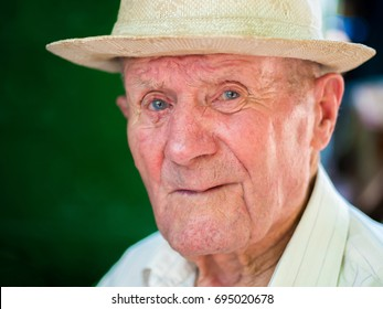 Very old man portrait with emotions. Grandfather happy and smiling. Portrait: aged, elderly senior. Close-up of a pensive old man in white hat sitting alone outdoors at summer.