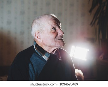 Very old man portrait. Grandfather. Aged, elderly, loneliness, senior with a small number of teeth. Face of man sitting alone.