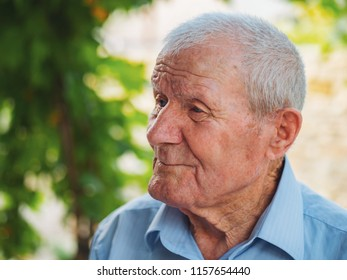 Very old man portrait. Grandfather relaxing outdoor at summer. Portrait: aged, elderly, senior. Close-up of old man sitting alone