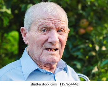 Very old man portrait. Grandfather is smiling and looking to camera. Portrait: aged, elderly, senior. Close-up of old man sitting alone outdoors.