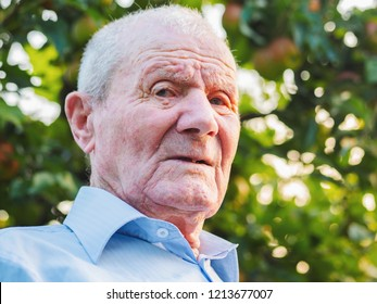 Very old man portrait. Grandfather is looking to camera. Portrait: aged, elderly, senior. Close-up of old man sitting alone outdoors.