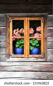 very old and picturesque blockhouse in the Austrian Alps with flowers behind the window