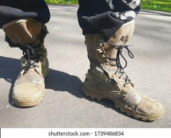 Las botas de los hombres rojos muy viejos en sus pies.