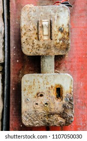 Very old, rusty and worn light switch with old style British round three pin 2A socket for low power lighting.